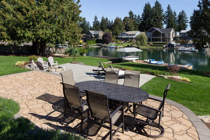 landscape architecture with stone tile patio overlooking a lake and dock