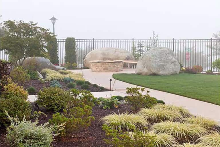 Landscape architecture with local, large stone barrier and stone fire pit