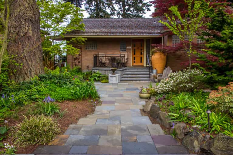 Landscape architecture with a blue stone walkway, native plants, and a morning coffee porch