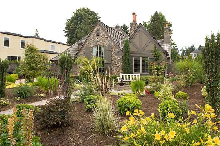 native plant and garden yard with stone walkway and fountain