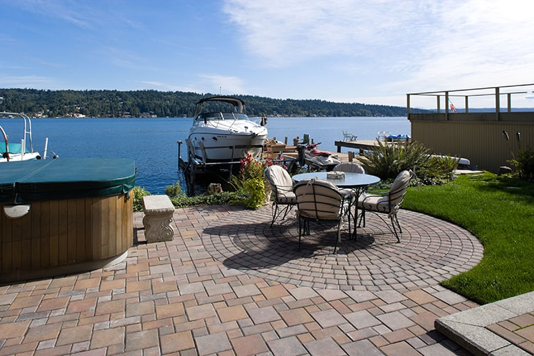 outdoor living area overlooking Lake Washington with stone patio and hot tub