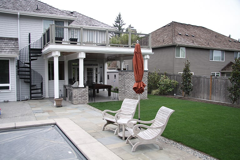 Outdoor living space with covered game room and stone walkway