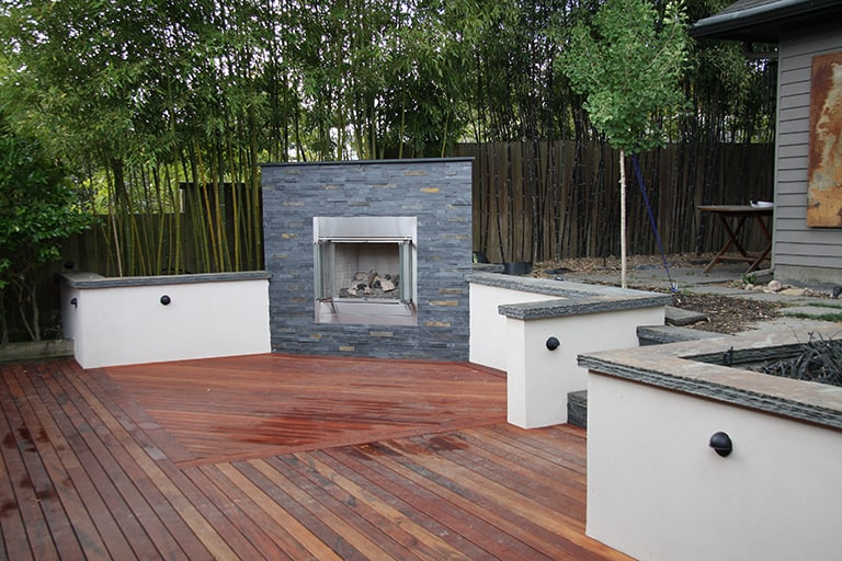 Outdoor living, grey stone fireplace with retaining wall with stone edge