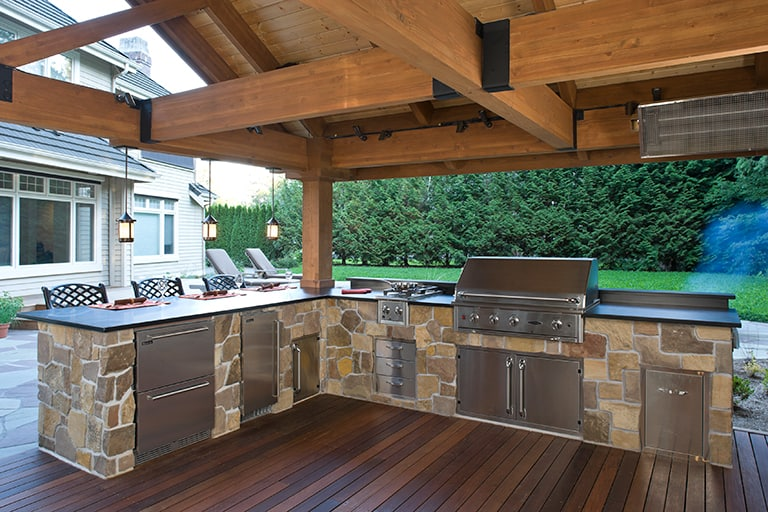 landscape architecture with covered patio, stone grill and kitchen space
