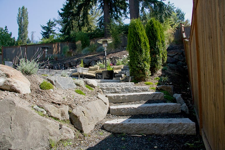 outdoor living, with rock retaining wall, stone steps and native vegetation